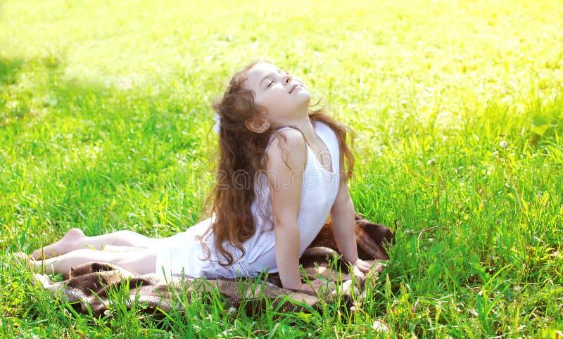 Niño que hace el ejercicio de la yoga que estira en hierba en verano soleado fotografía de archivo libre de regalías