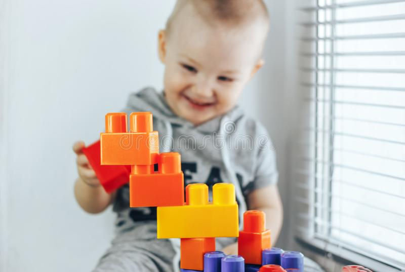 Niño que hace ladrillos del juguete Torre del juguete Bebé feliz foco en los juguetes Bebé unfocused fotos de archivo