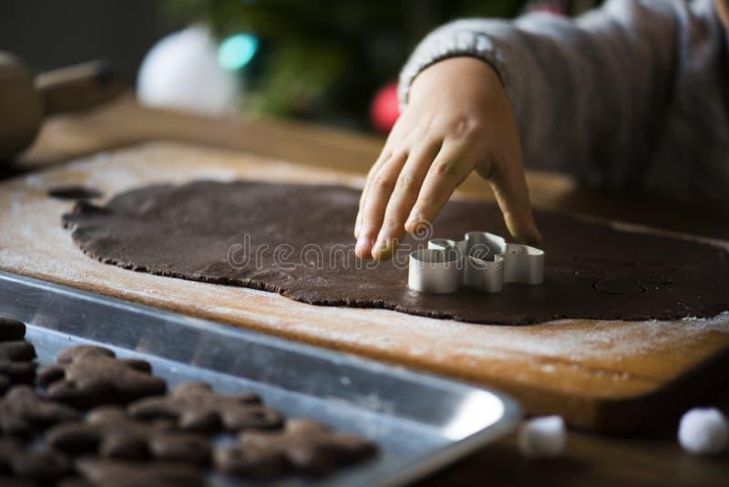 Niño que hace las galletas del chocolate de la Navidad fotos de archivo