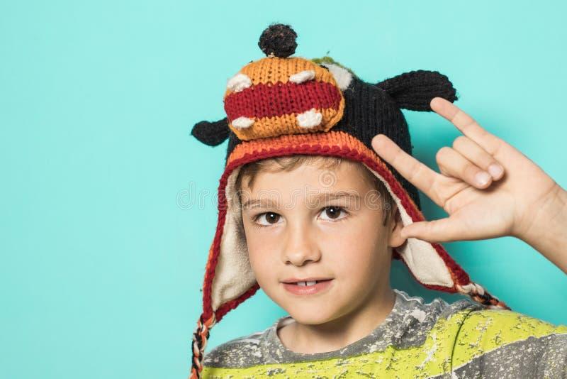 Niño que hace los cuernos con un sombrero divertido imagen de archivo libre de regalías