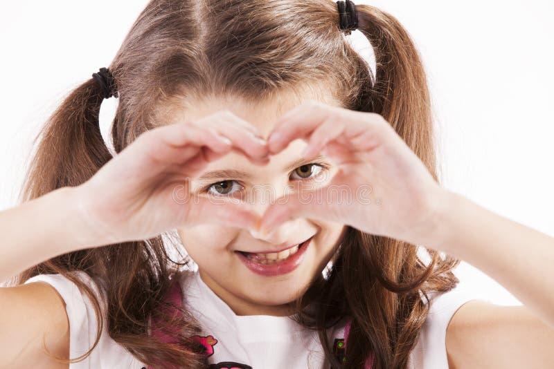 Niño que hace un corazón con sus manos fotos de archivo