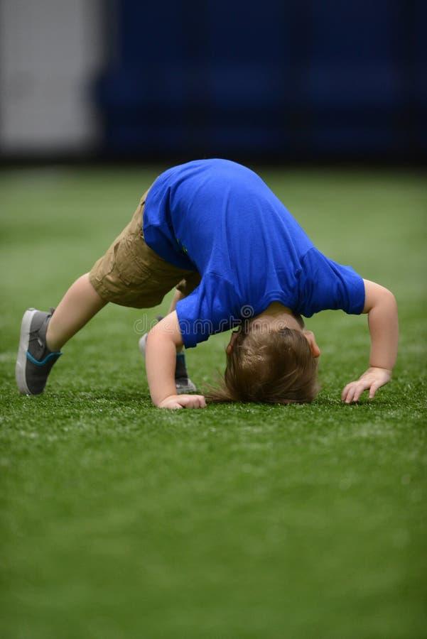 Niño que intenta hacer caer o una voltereta en la gimnasia fotos de archivo