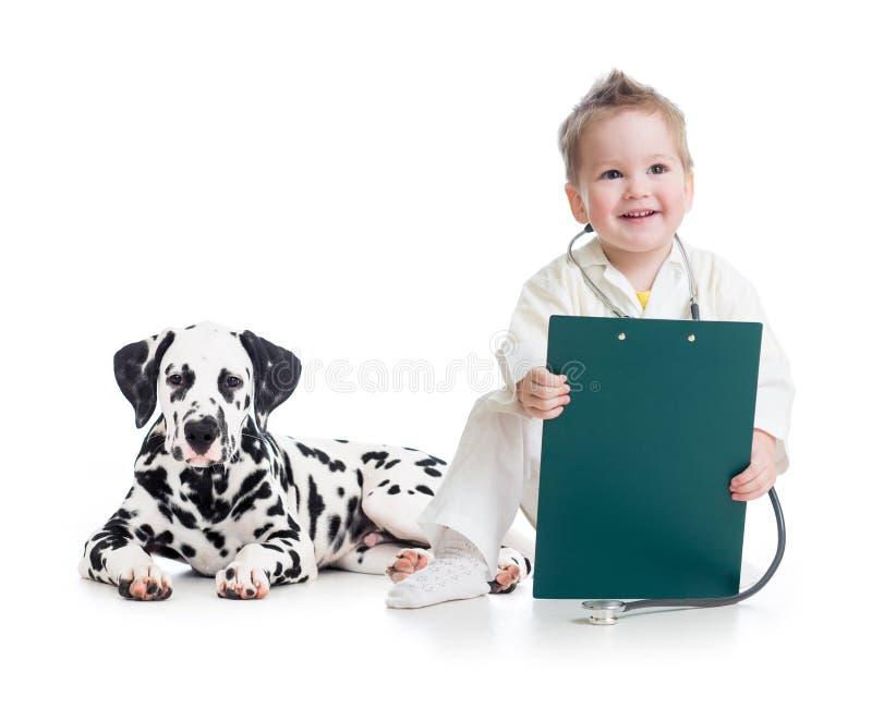 Niño que juega al doctor con el perro imagen de archivo