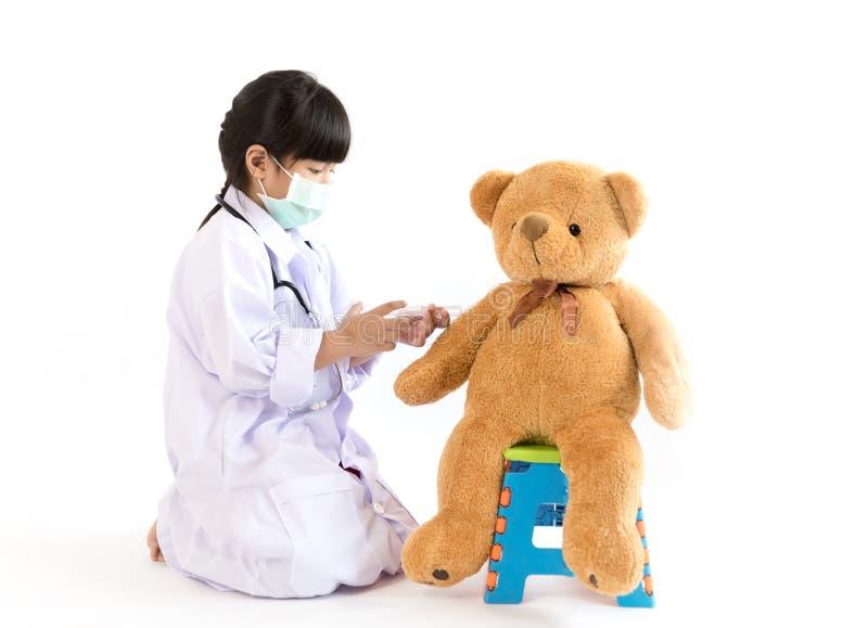Niño que juega al doctor con la inyección al oso de peluche imágenes de archivo libres de regalías
