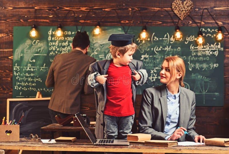 Niño que juega al juego Concepto el enseñar casero El niño elegante en casquillo graduado le gusta estudiar Padres que enseñan al fotografía de archivo libre de regalías