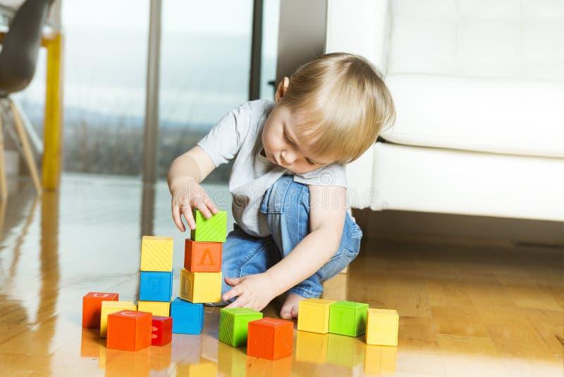 Niño que juega bloques del juguete dentro de su casa foto de archivo