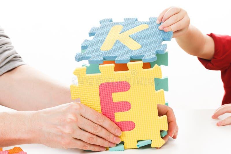 Niño que juega con alfabeto del ABC de los bloques del rompecabezas, escuela foto de archivo