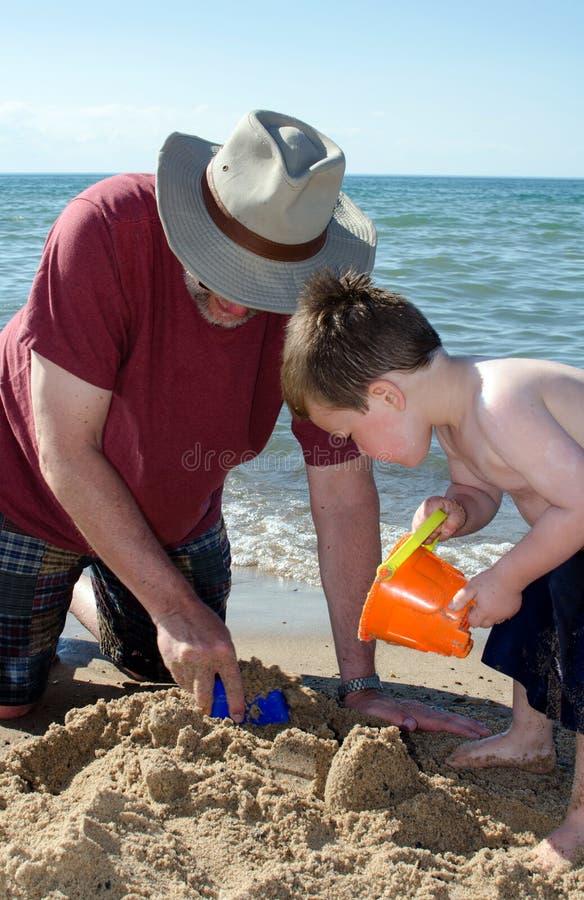 Niño que juega con el abuelo en una playa de Indiana fotos de archivo
