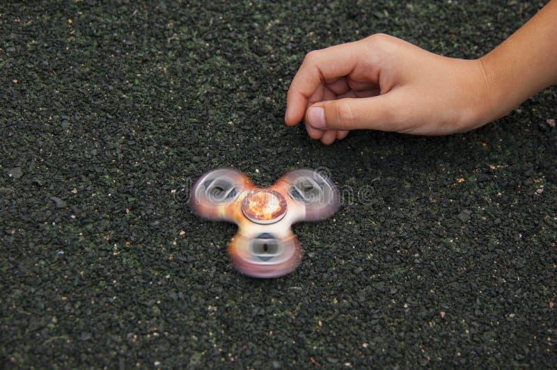 Niño que juega con el artilugio popular imagenes de archivo