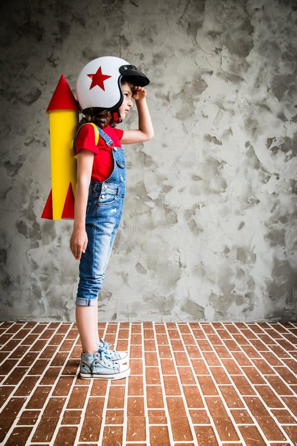 Niño que juega con el cohete de la cartulina foto de archivo
