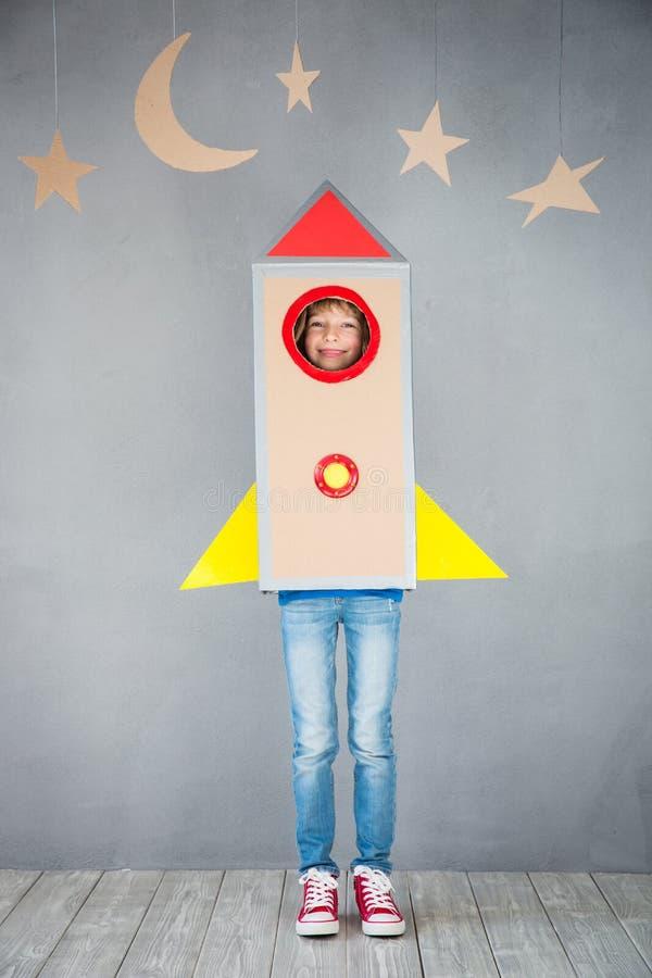 Niño que juega con el cohete de la cartulina en casa imagenes de archivo