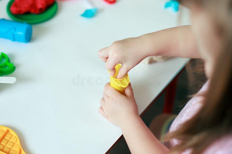 Niño que juega con la arcilla colorida que moldea diversas formas - primer en las manos, espacio de la copia imagen de archivo libre de regalías