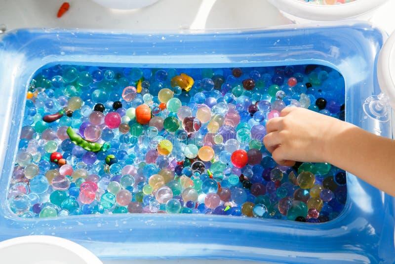 niño que juega con la bola de cristal coloreada, jugando al juego con las bolas coloreadas imagen de archivo