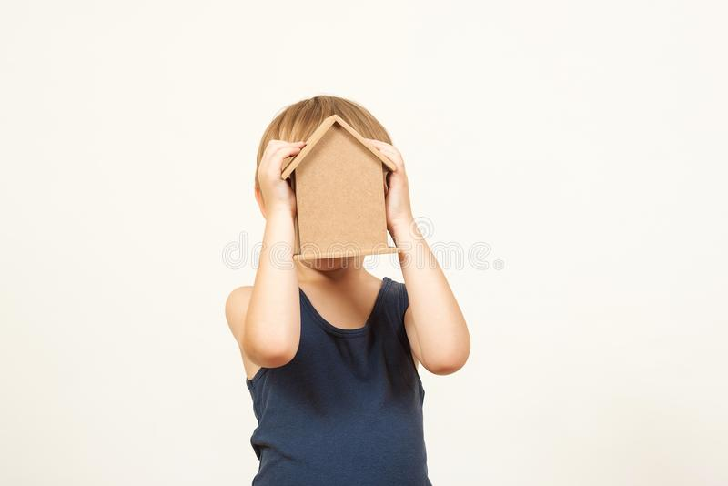 Niño que juega con la casa de los juguetes El pequeño niño ocultó su cara detrás de una pequeña casa Niño que sostiene la pequeña foto de archivo