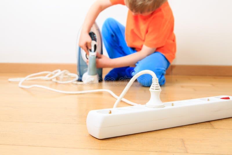 Niño que juega con la electricidad, seguridad de los niños foto de archivo