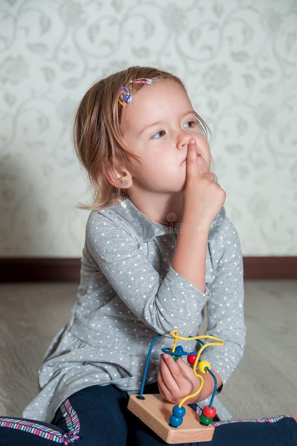 Niño que juega con laberinto Niña que piensa un finger cerca de la boca Juguete educativo fotos de archivo libres de regalías