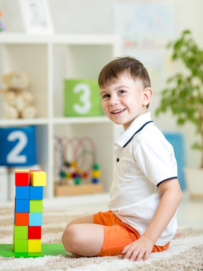 Niño que juega con las unidades de creación en casa o guardería foto de archivo