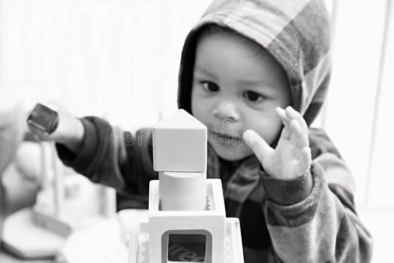 Niño que juega con los bloques de los juguetes imagen de archivo
