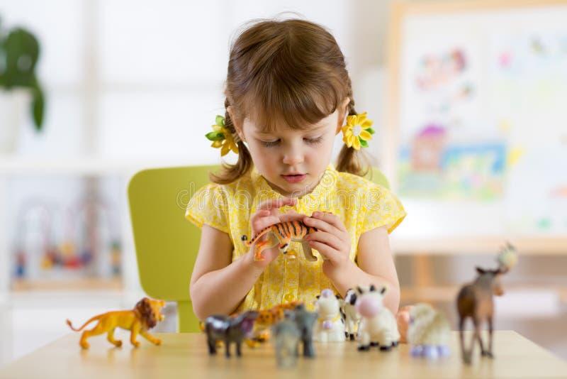 Niño que juega con los juguetes animales en la tabla en guardería u hogar fotografía de archivo libre de regalías