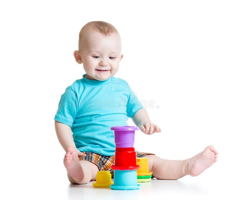 Niño que juega con los juguetes del color foto de archivo