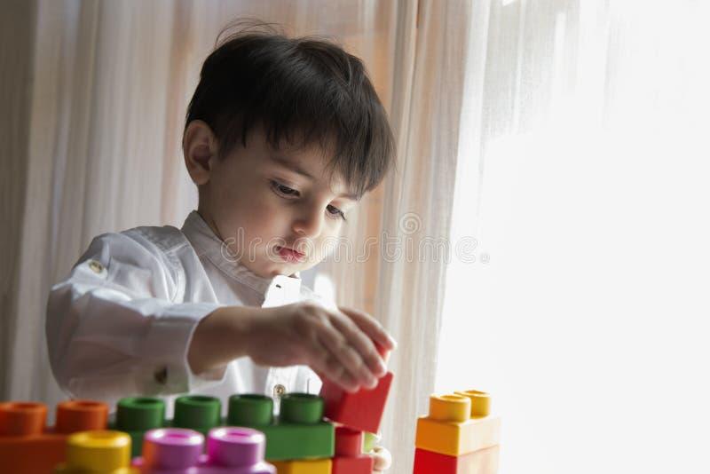 Niño que juega con los ladrillos plásticos coloridos fotos de archivo libres de regalías