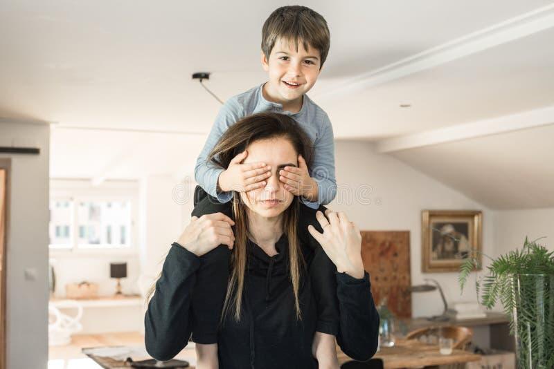 Niño que juega con su madre en casa Hijo y una madre con la expresión y la sonrisa felices imágenes de archivo libres de regalías
