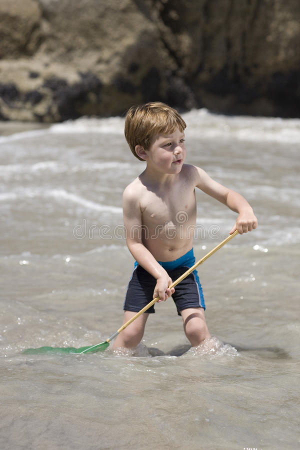 Niño que juega con una red de pesca. foto de archivo libre de regalías