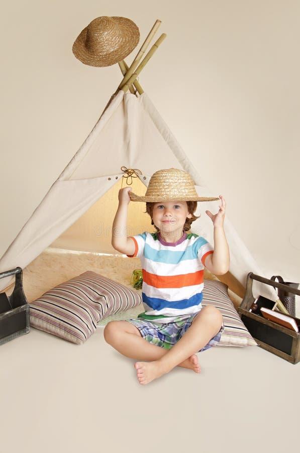 Niño que juega dentro con la tienda de la tienda de los indios norteamericanos imagen de archivo