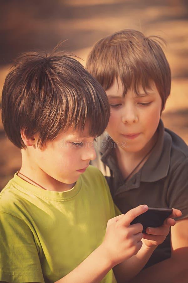 Niño que juega el teléfono móvil al aire libre foto de archivo