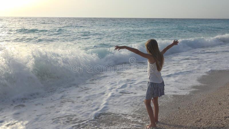 Niño que juega en la playa, muchacha que mira las ondas del mar, niño que mira en la costa imagen de archivo libre de regalías