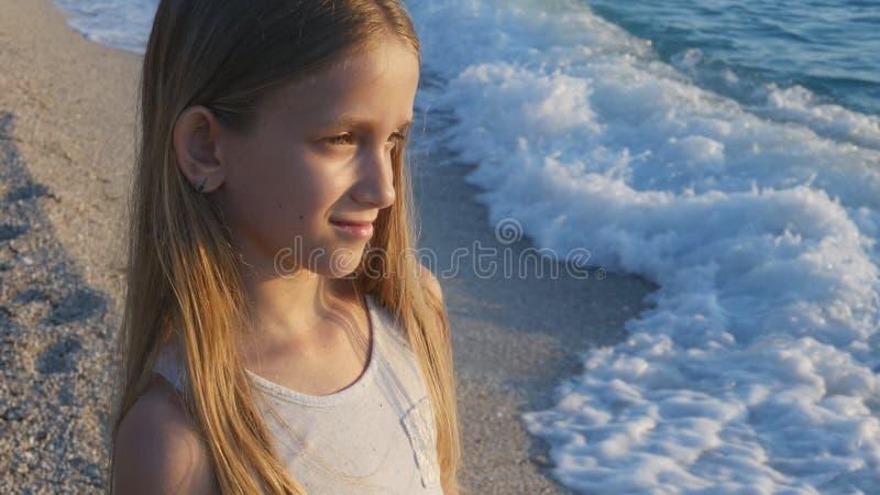 Niño que juega en la playa en puesta del sol, ondas de observación del mar del niño, retrato de la muchacha en orilla imágenes de archivo libres de regalías