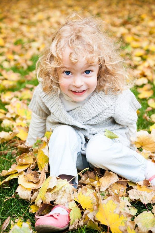 Niño que juega en parque del otoño foto de archivo