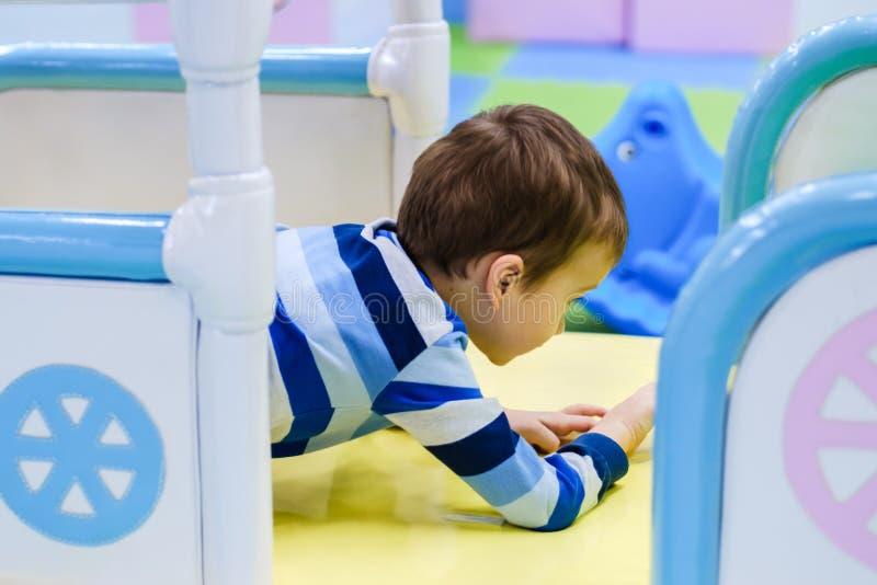 Niño que juega en tienda del juguete Juguetes y juego educativos del papel para los niños Guardería o sitio del juego del preesco imagenes de archivo