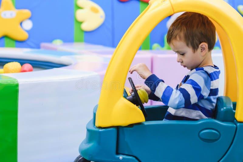 Niño que juega en tienda del juguete Juguetes y juego educativos del papel para los niños Guardería o sitio del juego del preesco imagen de archivo