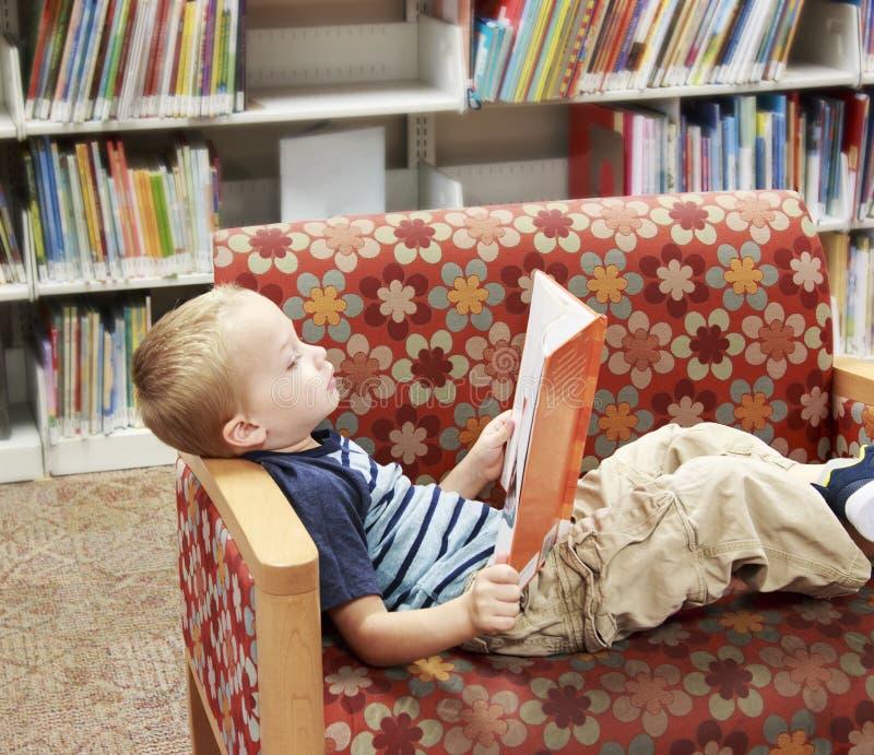 Niño que lee un libro en un sofá en la biblioteca fotografía de archivo