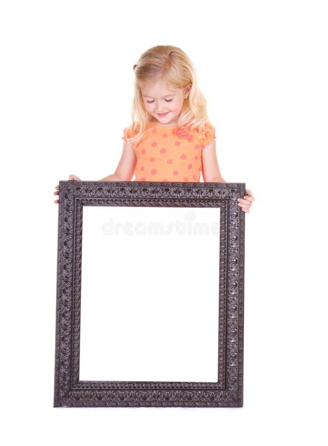 Niño que lleva a cabo el marco en blanco foto de archivo