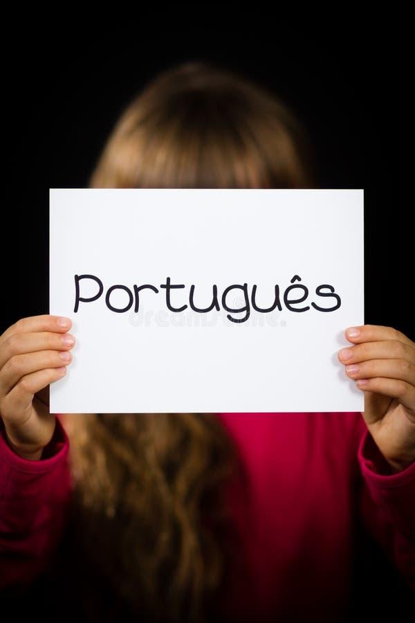 Niño que lleva a cabo la muestra con la palabra portuguesa Portugues - portugués i fotografía de archivo libre de regalías