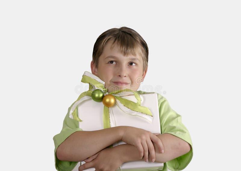 Niño que lleva a cabo un presente envuelto y que mira cuidadosamente para arriba fotografía de archivo