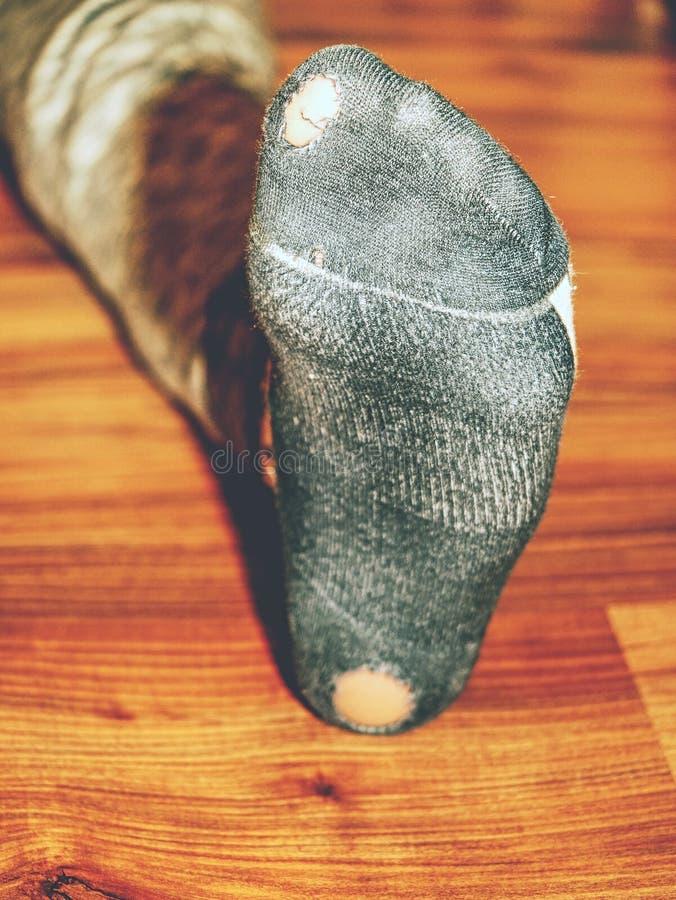 Niño que lleva calcetines sudorosos con los agujeros en talón fotografía de archivo