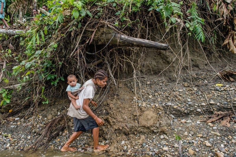 Niño que lleva de la mujer del Papuan en ella detrás imagen de archivo