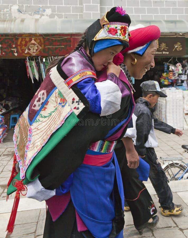 Niño que lleva de la mujer tibetana imagen de archivo libre de regalías