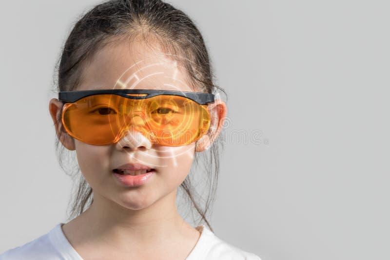 Niño que lleva el dispositivo elegante futurista de los vidrios que exhibe la información de Digitaces en concepto aumentado de l fotos de archivo