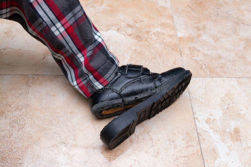 Niño que lleva el zapato de cuero gravemente roto fotografía de archivo