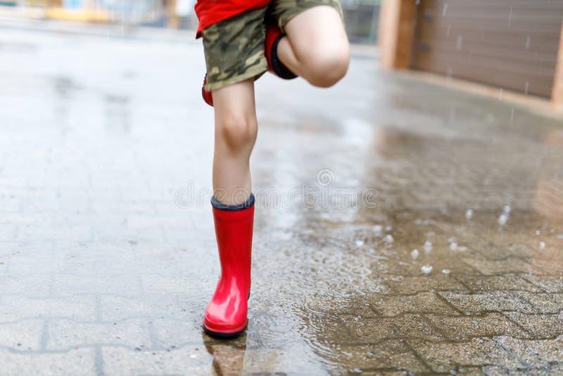 Niño que lleva las botas de lluvia rojas que saltan en un charco Cierre para arriba Niño que se divierte con salpicar con agua Pe imágenes de archivo libres de regalías