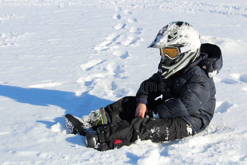 Niño que lleva un casco Biking que se sienta en la nieve foto de archivo libre de regalías