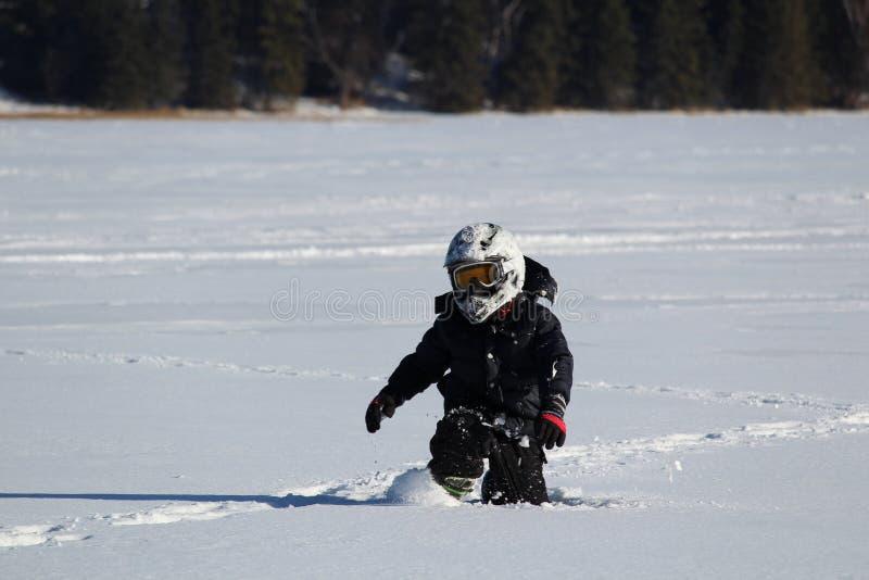Niño que lleva un OHV que camina a través de nieve profunda foto de archivo libre de regalías