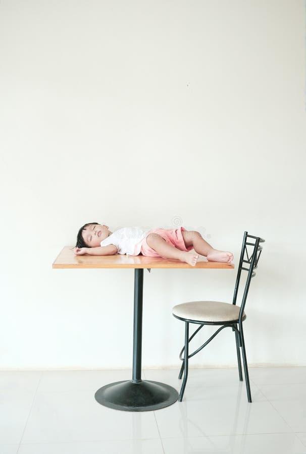 Niño que miente en lugar incorrecto Alguien bebé puesto en la mesa de comedor foto de archivo libre de regalías