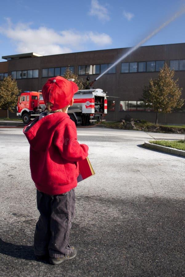 Niño que mira el coche de bomberos foto de archivo libre de regalías