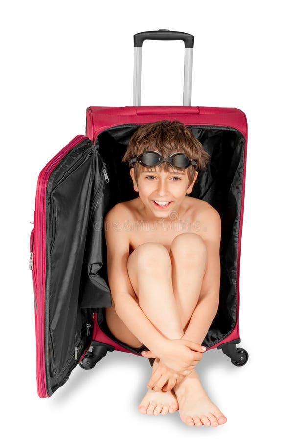 Niño que mira hacia fuera la maleta roja fotografía de archivo
