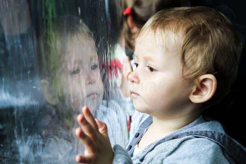 Niño que mira la lluvia en ventana fotos de archivo